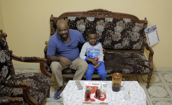 Sudanese activist Tayeb Ibrahim, who had worked to expose Sudanese abuses in the volatile South Kordofan province and hopes to see family living in the U.S. state of Iowa, watches television with his son Mohammed, in Cairo, Egypt, Wednesday, June 28, 2017. Dozens of Sudanese activists living in Egypt as refugees, many of whom fled fundamentalist Islamic militias and were close to approval for resettlement in the United States, now face legal limbo in Egypt after the Supreme Court partially reinstated President Donald Trump's travel ban. (Amr Nabil/Associated Press